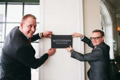 GM Tim Ostrem (left) and Marriott VP Manlio Marescotti hang the Autograph sign at the reopening of the Algonquin Resort