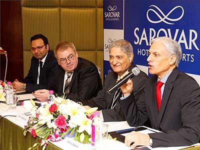 Executives from Louvre Hotels Group and Sarovar Hotels announce the acquisition.