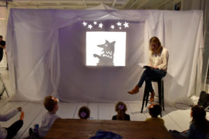 Tracey Hecht reads one of her books in front of shadow puppets.